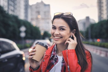 Beautiful smiling young woman in red jacket with coffee cup on modern city street, she is happy, listening music in headphones.