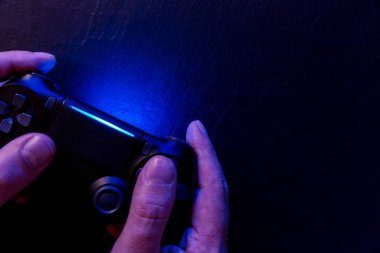 Man playing video game with controller at night with lights