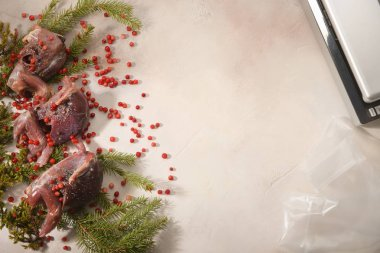 Wild hunting fowls in cooking. Ptarmigan, fir-tree branches and cowberry arranged on light background. Sous Vide cooking.