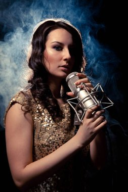 Picture of beautiful singer in gold dress with studio microphone and steam