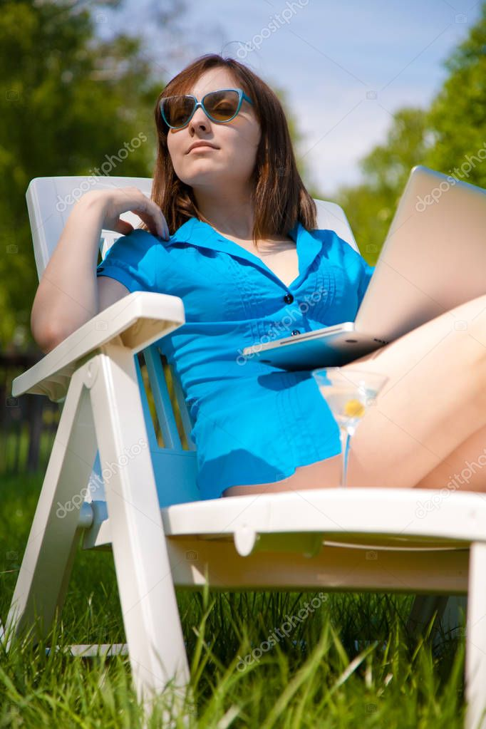 Businesswoman with laptop and glass of martini rest outdoors