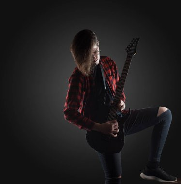 handsome musician playing guitar on the black background