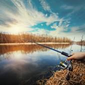 Kézzel horgászbot és orsó a nyári tó
