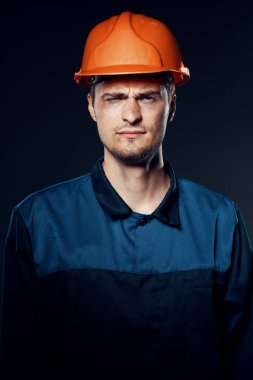 young man in work wear and helmet. Studio shot