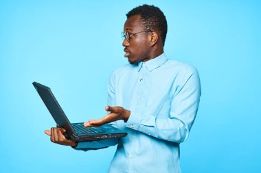 Young african surprised  businessman holding laptop isolated on blue background
