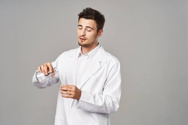 Doctor in lab coat with test tubes on grey background. Studio shot