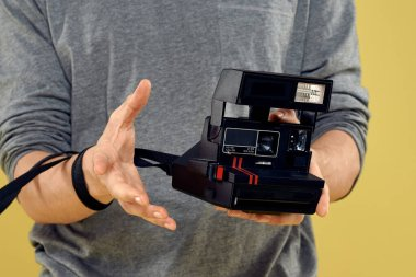 Photo camera in the hands of a man professional equipment hobby Creative approach studio cropped view