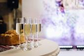 abgeschnittene Ansicht von Gläsern mit Champagner und gebackener Torte auf weißem Tisch