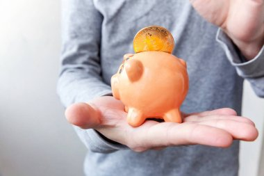 Piggy bank, hand holds golden bitcoin coins virtual money. Cryptocurrency and saving concept