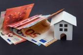 Fotografie Euro bankovky a symbolické malé hračky dům. Koupi nemovitosti a hypotéka