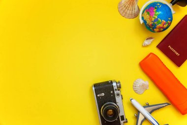 Flat Lay with sunscreen, plane, vintage camera, passport, globe, sunglasses and shell on yellow colourful trendy modern fashion background. Vacation travel summer weekend sea adventure trip concept