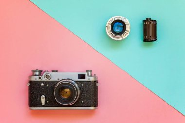 SAINT-PETERSBURG, RUSSIA - APRIL 13, 2018: Vintage film photo camera lens film roll and accessories on pink and blue colourful pastel trendy modern fashion pin-up background. Technology development photographer hobby classic memory trip concept. Top