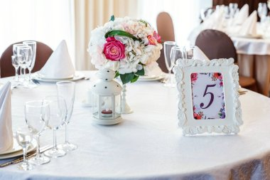 Glasses, flowers, fork, knife, napkin folded in a pyramid, served for dinner in restaurant with cozy interior. Wedding decorations and items for food, arranged by the catering service on a large table covered with white tablecloth