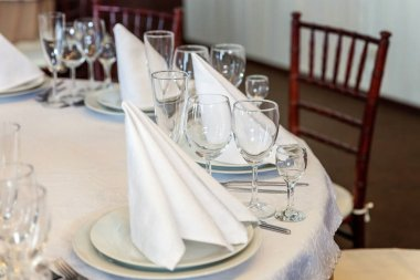 Glasses,  napkin folded in a pyramid, served for dinner in restaurant with cozy interior. Wedding decorations and items for food, arranged by the catering service on a large table covered with white tablecloth