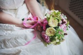 Podrobnosti o svatební šaty a ruce nevěsty kroužek s kyticí