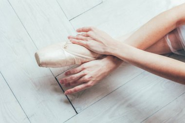 Hands of ballerina in blue tutu skirt puts on pointe shoes on leg in white light hall. Young classical ballet dancer woman in dance class