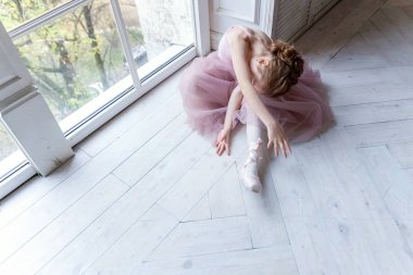 Closeup of young ballerina sit in pointe shoes at white wooden floor background, with copy space. Ballet practice. Beautiful slim graceful ballet dancer.