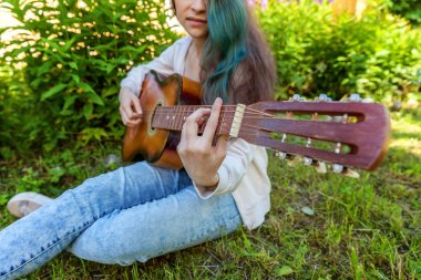 Young woman sitting in grass and playing guitar