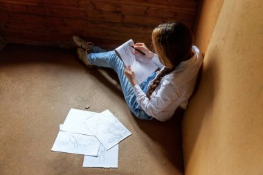 Young hipster woman sitting on floor and drawing sketch in album at home. Teen girl learning sketching picture in her room