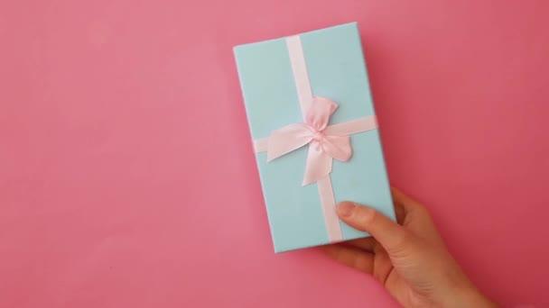 Jednoduše navrhnout ženskou ruku držení modrého dárkového boxu izolované na růžovém pastelově barevném módním pozadí