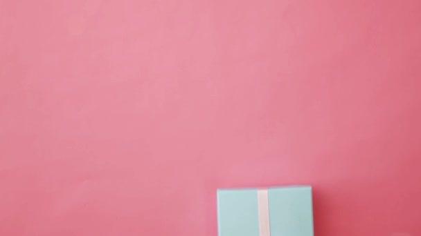 Jednoduše Navrhněte ženskou ruku, která drží modrou dárkovou schránku izolovanou na růžovém pastelově barevném módním pozadí. Vánoce Nový rok narozeninová oslava současná romantická představa. Kopírovat místo
