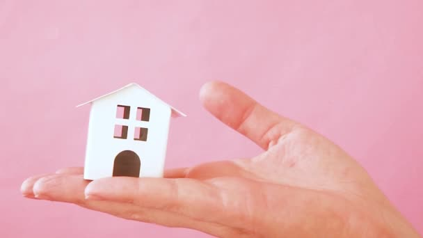 Simply design female woman hand holding miniature white toy house isolated on pink pastel colorful trendy background. Mortgage property insurance dream home concept. Copy space