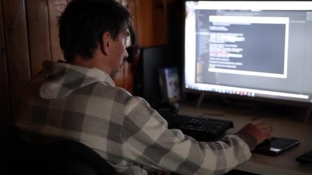 Koncept programování. Muž programátor pracující na počítači doma kódování na obrazovce psaní kódu. Programátor IT inženýr pracující na zadávacích kódech projektu