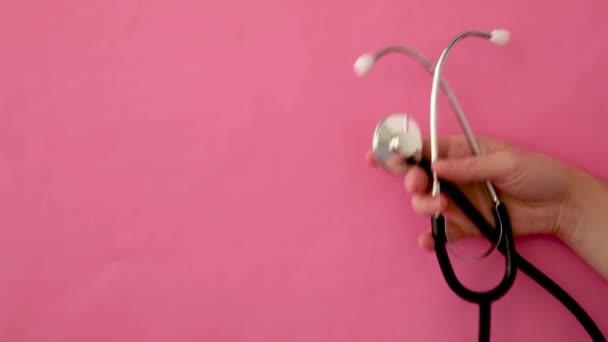 Jednoduše minimální design žena ruční držení lékařského vybavení stetoskop nebo fonendoskop izolované na trendy pastelové růžové pozadí. Přístrojové zařízení pro lékaře. Pojetí životního pojištění zdravotní péče