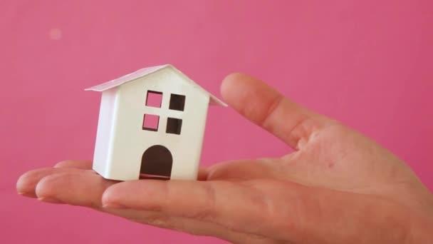 Egyszerűen design női nő kéz gazdaság miniatűr fehér játék ház elszigetelt rózsaszín pasztell színes trendi háttér. Jelzálog ingatlan biztosítás álom otthon koncepció
