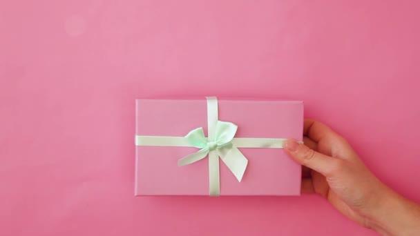 Jednoduše design žena ruka drží růžové dárkové krabice izolované na růžové pastelové barevné trendy pozadí. Vánoční novoroční narozeninová valentýnská oslava představuje romantický koncept. Kopírovat prostor