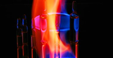 medical ampoules on fire. on a black background. toned fire.