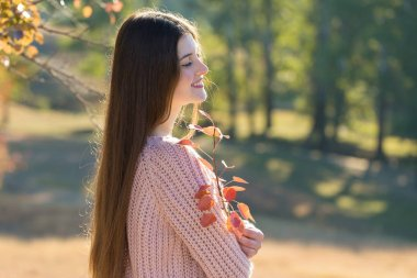 Portrait of pretty young woman in stylish knitted sweater standing on the golden autumn forest on sunny day