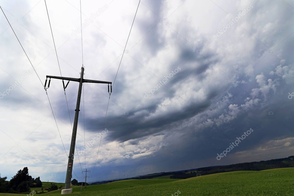 A storm in the sky over an overhead line mast. Dark rain clouds in the sky over a power line