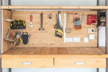 Wooden workbench at workshop. Lot of different tools for diy and repair works. Wood desk for product placement. Copyspace. Labour day