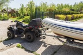 Photo Transportation of inflatable boat on trailer. ATV quadbike moves ship to lake or river shore for launching. Beginning of water navigation and fishing season.