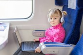Fotografie Little cute girl travelling by train. Kid listening to music or watching movie with laptop and white headphones. Children activity and entertainment during trip concept.