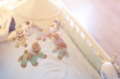 Photo Close-up baby crib with musical animal mobile at nursery room. Hanged developing toy with plush fluffy animals. Happy parenting and childhood, expectation delivery of a child concept