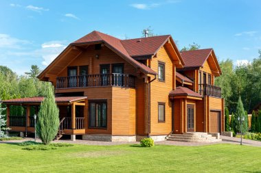 Beautiful luxury big wooden house. Timber cottage villa with with green lawn, garden and blue sky on background.