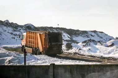 Dump trucks unloading waste over huge sanitary fill. Environmental pollution. Out of date technology.