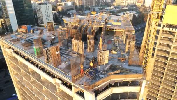 Top of high tower building with workers on construction site. Big city development. Metropolis. Aerial view