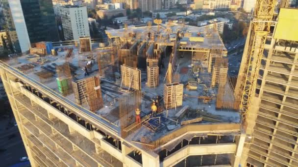 Top of high tower building with workers on construction site. Big city development. Metropolis. Aerial view.