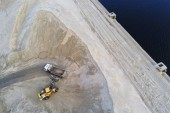 Fotografie Big heavy wheel loader loading sand into dump truck in sand pit. Heavy industrial machinery concept