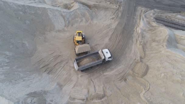 Großer schwerer Radlader lädt Sand in Kipper in Sandgrube. Konzept für schwere industrielle Maschinen