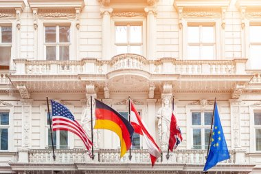 National flags on old building facade in european city. Flags of USA, Germany, Austria, European Union and folded Great Britain flag. Brexit concept.