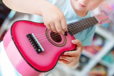 Little cute blond girl having fun learning to play small ukulele guitar at home.Toddler girl playing toy musical instrument indoors.