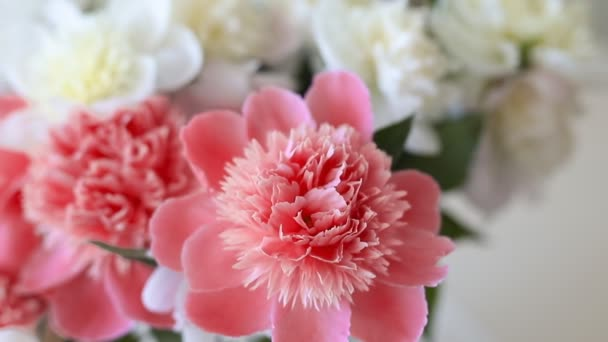 Bouquet of fresh big coral pink, white and cream peonies in simple glass jar on glance table indoor. Vase with beautiful tender spring flowers on glass table