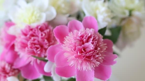 Kytice čerstvě velkých korálově růžových, bílých a smetanových pivoňek v jednoduché skleněné sklenici na skleněném stole uvnitř. Váza s krásnými křehkými jarními květinami na skleněném stole