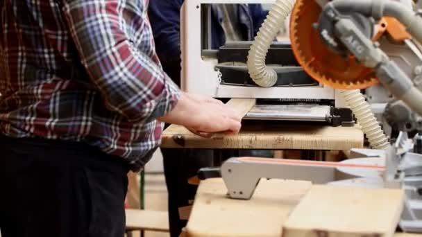 Řemeslník pracuje v truhlářství s spoustou moderních profesionálních elektronářadí. Muž používající hustou pilu a kotoučový pilník a jiné vybavení v dílně