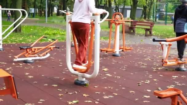 Senioren und Jugendliche turnen und trainieren auf dem öffentlichen Außengelände der Turnhalle am Stadtpark. Konzept eines gesunden Lebensstils