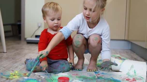Adorable cute caucasian little blond siblings children enjoy having fun together with mother painting brush and palm at home indoors . Cheerful happy kids smiling drawing masterpiece art picture.